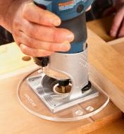Cutting a dado, with the flat side of a Veritas compact router base plate registered against a fence