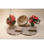 Both sizes of basket liners sitting in front of two baskets with liners in them, one filled with a flowering plant and hanging from chains, alongside a flowering potted plant