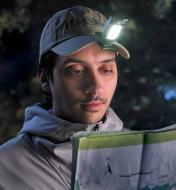 Reading a map in low light with the multi-function LED headlamp clipped to a cap brim