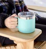 Yeti Rambler mug held on the armrest of an Adirondack deck chair
