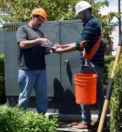 A man uses a Bucket Buddy Sash to hold a pail off the ground, freeing his hands to fill out forms