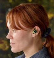 A woman wearing ISOtunes Free wireless electronic hearing protectors