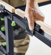 Clipping a wooden support onto the frame of the mobile sawing table