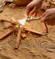 Personne frottant l'allume-feu avec le percuteur pour faire une pluie d'étincelles sur du bois d'allumage