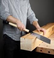 Personne effectuant une coupe dans une épaisse poutre en bois avec la scie kataba convexe à tronçonner
