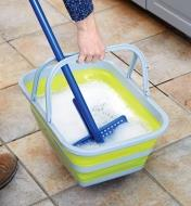 Rinsing a mop in a collapsible tote filled with soapy water.