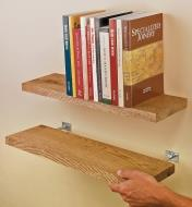Two pairs of blind shelf supports installed in wooden shelves and mounted to a wall