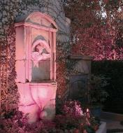Color-controlled LED (RGB) landscape light installed by a garden fountain