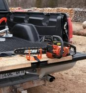 Vise clamped onto a chain-saw blade and tied to a truck tailgate with the included strap