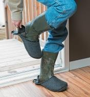 Man putting on second boot slipper over muddy boot before coming inside
