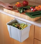 Scooping food waste from a cutting board into a countertop collection bin hung over the outside of a cupboard door