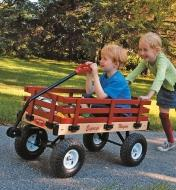 A girl pushes a boy in the All-Season Convertible Wagon with wheels on