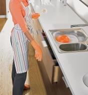 A woman washing dishes pushes a drawer front to open the drawer