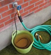Brass Siphon Mixer connected between a faucet and hose, with the siphon line resting in a pail of fertilizer
