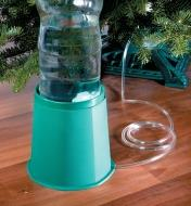 Christmas Tree Water Fountain beside a Christmas tree with the tube inserted in the tree stand reservoir