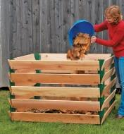 A woman pours leaves into a completed composter with wooden boards attached to the brackets
