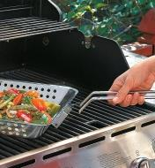 Detaching the handle from the Barbecue Grilling Basket that is sitting on the grill, filled with vegetables