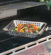 Panier de cuisson pour barbecue rempli de légumes et posé sur la grille d'un barbecue