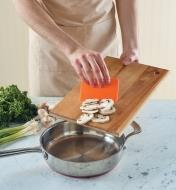 Using the food prep scraper to transfer sliced mushrooms from a cutting board into a saucepan