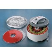 Food Dehydrator containing fresh fruit slices, with a filled fruit roll sheet and extra trays sitting beside it