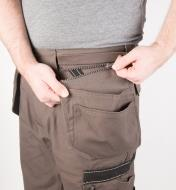 A man wearing gray work pants unzips one of the side pouches