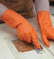 A person wearing Heavy-Duty Latex Gloves scrapes paint from a door.