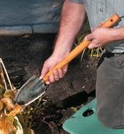 Digging in a garden with a long-handled trowel
