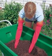 A woman wearing Elbow-Length Mucking Gloves reaches into a wheelbarrow full of compost