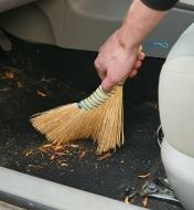 Using the Dutch Hand Broom to sweep out the floor of a car