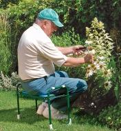 A man sits on the folding kneeler stool while cutting flowers