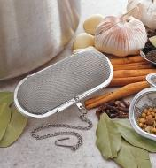 Herb & Spice Infuser on a counter beside a pot and among various herbs and spices