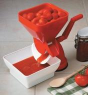 Tomato press sits on a counter with the hopper full of whole tomatoes and pulp running into the catch bowl
