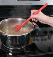 Stirring soup on a stovetop with the High-Heat Spoon