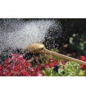 Haws Brass Water Wand watering flowers outdoors