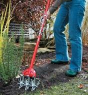 A Garden Weasel being used in a garden