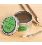 An open tin of grafting wax next to a several twigs