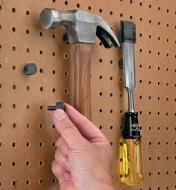 Magnetic Studs installed in pegboard, holding a hammer and a chisel