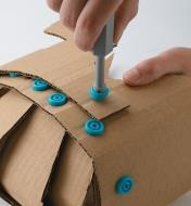 Fastening cardboard together using Makedo plastic screws and screwdriver