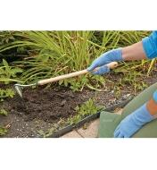 Digging in a flower garden using the Mid-Length Trenching Hoe