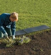 A woman uses a pair of kneeling strips to create a longer kneeling area in a garden