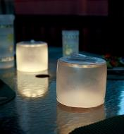 Two frosted Luci lanterns illuminating an outdoor table