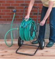 A woman winds a hose onto the Hose Reel Cart