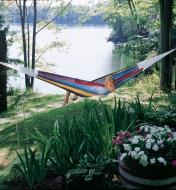 A person lies crossways on a Mayan Hammock hung between trees by a lake