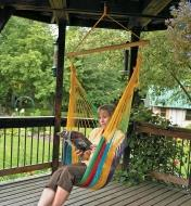 A woman relaxes in a Mayan Hammock Chair hanging in a covered porch