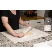 Rolling out dough on the pastry cloth using a rolling pin with a cover on it