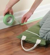 Kneeling on the Portable Canvas Utility Cushion while applying painter's tape to a floor