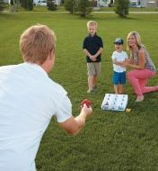 A family plays a game of Pitch-n-Hole at a park