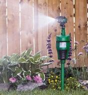 Pest-Deterring Jet Sprayer installed in a flower garden, spraying a burst of water