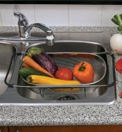 Over-the-Sink Colander suspended over a sink and filled with vegetables