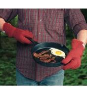 Gants de cuisine portés pour manipuler une poêle à frire en fonte